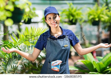 pretty female gardener with arms open in greenhouse - stock photo