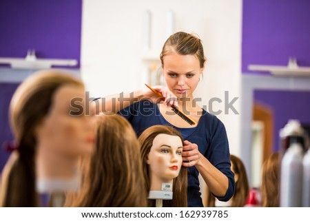 Pretty female hairdresser/haidressing apprentice/student training on an apprentice head - stock photo