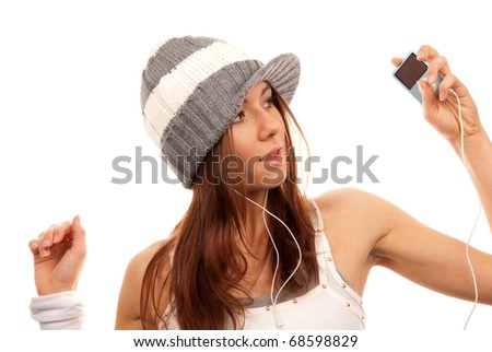 Pretty female in headphones listening music and  looking  her new modern mp3 player isolated on a white background - stock photo