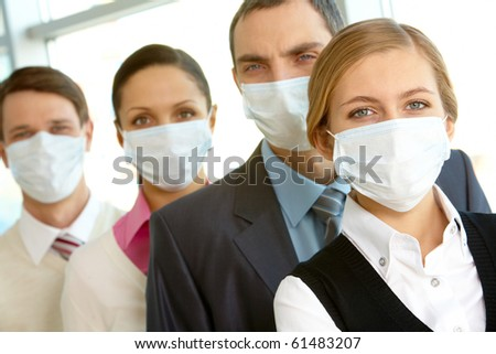 Pretty female in protective mask looking at camera on background of business people