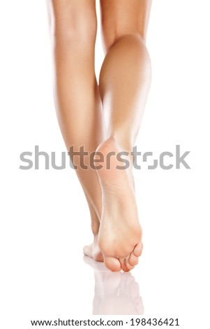 pretty female legs and bare feet on white background - stock photo