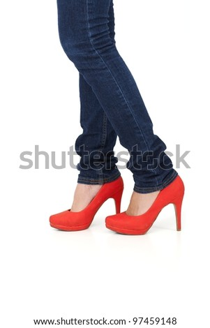 Pretty female legs in red high heel shoes and jeans, cutout on white. - stock photo