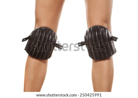 pretty female legs with high heels, and with knee protectors - stock photo
