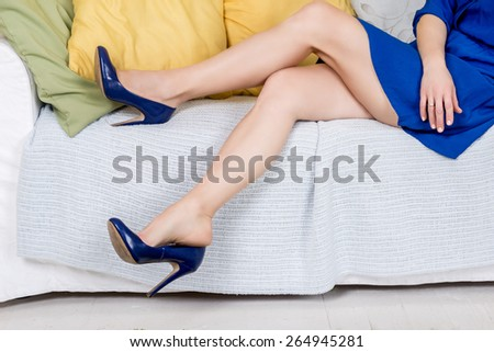 pretty female legs with high heels on sofa - stock photo
