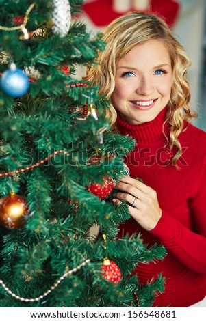 Pretty female looking at camera out of decorated firtree - stock photo
