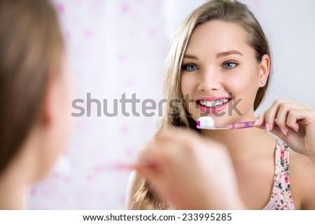 Pretty female looking in mirror while brushing teeth, dental hygiene  - stock photo