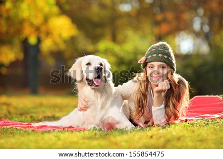 Pretty female lying down with her labrador retriever dog in a park - stock photo