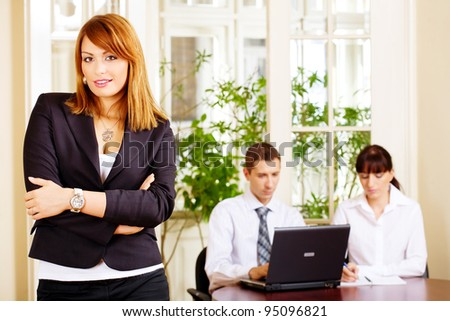 Pretty female manager with employers in office