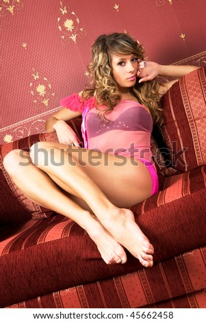 Pretty female model i on the red sofa.