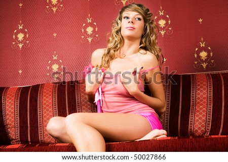 Pretty female model on the red sofa