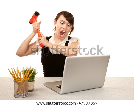 Pretty female office worker destroying laptop computer - stock photo
