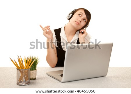 Pretty female office worker with laptop computer and headphones - stock photo