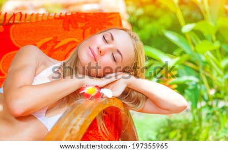 Pretty female on tropical resort, lying down on deckchair with closed eyes and taking sun bath, enjoying exotic nature, summer vacation concept - stock photo