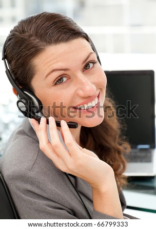 Pretty female representative on the phone with earpiece on sitting at her desk - stock photo