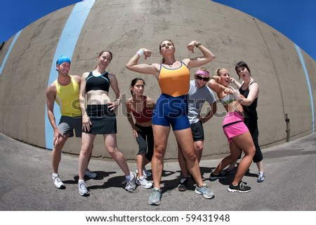 Pretty female runner poses and flexes with friends - stock photo