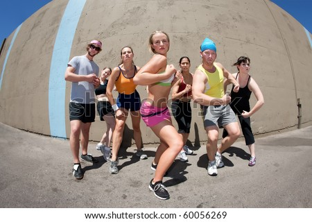 Pretty female runner poses with fellow athletes - stock photo