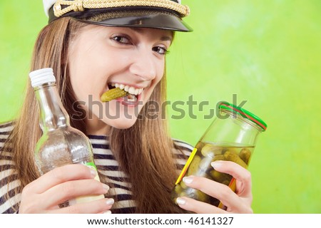 Pretty female sailor with bottle of vodka and pickle over green - stock photo