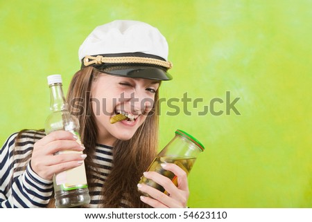 Pretty female sailor with bottle of vodka and pickle over green background - stock photo