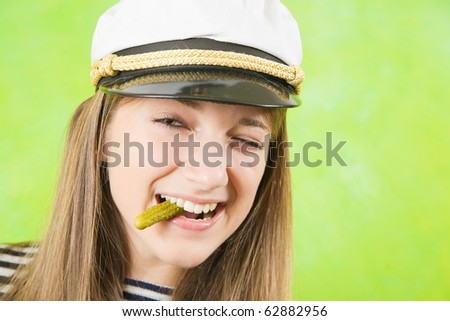 Pretty female sailor with  pickle over green background - stock photo