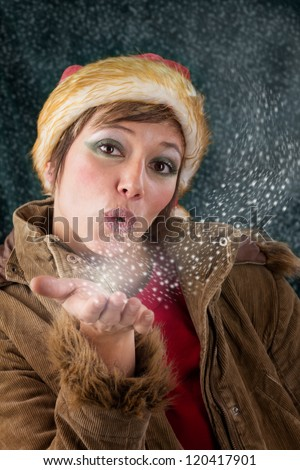 Pretty female Santa Claus as christmas fairy blowing a kiss out of snow and stars. Sensual studio portrait against a dark green background.