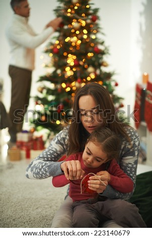 Pretty female showing her little daughter how to knit with man decorating xmas tree on background - stock photo