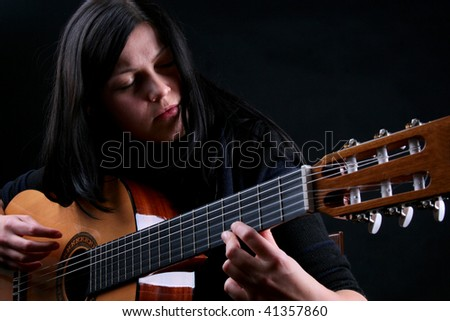 Pretty female singer playing guitar - stock photo