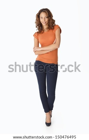 Pretty female standing arms crossed over white background, smiling.