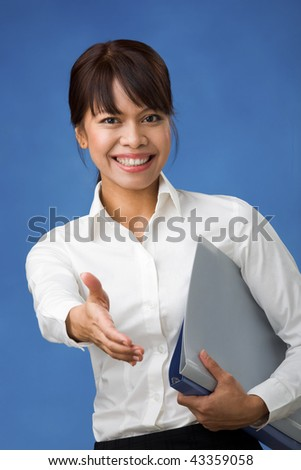 Pretty female stretching her arm for handshake while looking at camera - stock photo