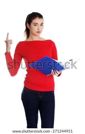 Pretty female student holding notebook pointing up.