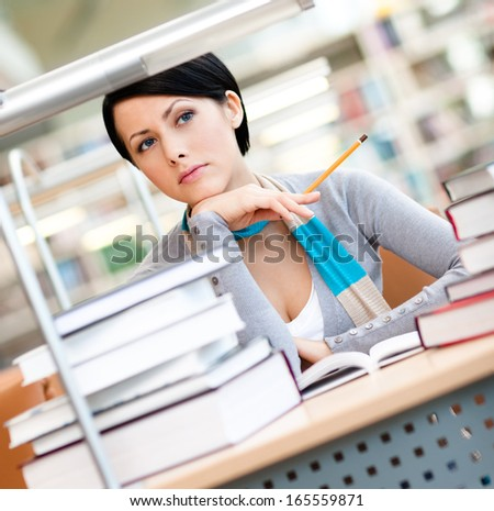 Pretty female student studies with piles of books sitting at the desk at the reading hall - stock photo