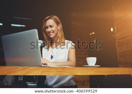 Pretty female student with cute smile keyboarding something on net-book while relaxing after lectures in University, beautiful happy woman working on laptop computer during coffee break in cafe bar - stock photo