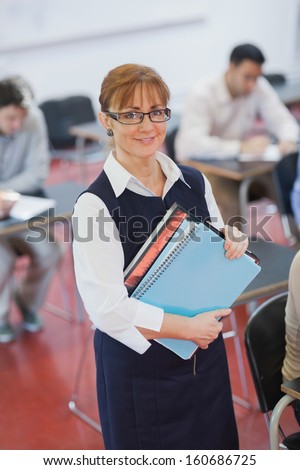 Pretty female teacher posing in her classroom holding some files smiling at camera - stock photo