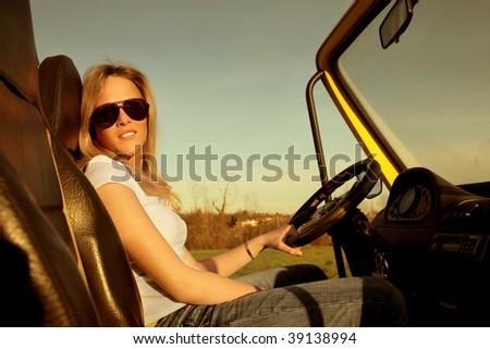 pretty female teen driving a car - stock photo