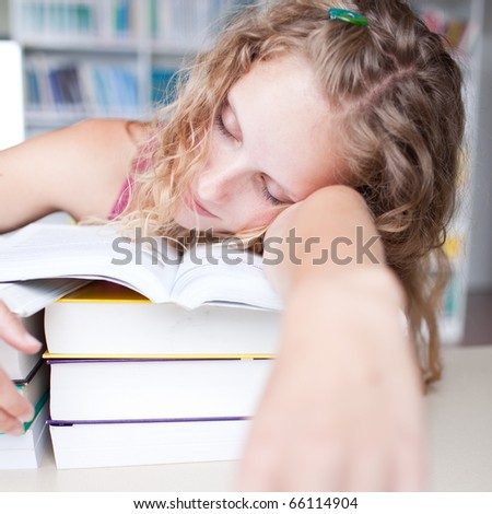 pretty female tired/exhausted/sleepy college student taking a nap  in a library (shallow DOF; color toned image) - stock photo