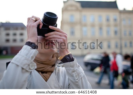 pretty, female tourist taking pictures in a city (shallow DOF; selective focus on the camera) - stock photo