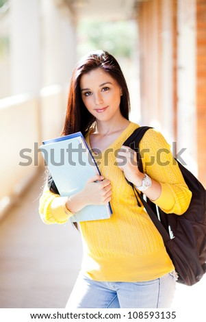 pretty female university student with books and backpack - stock photo