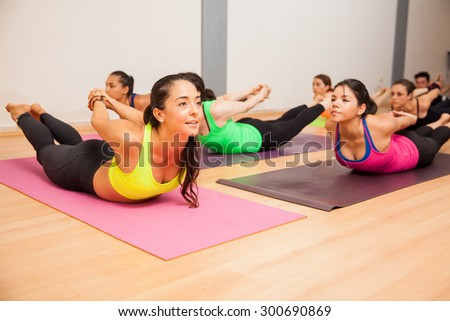 Pretty female yoga instructor and her students doing the locust pose during class