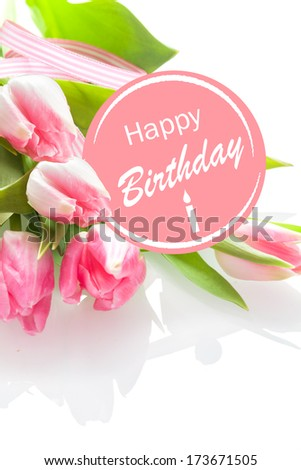 Pretty feminine Happy Birthday greeting with a festive pink rosette and a bouquet of beautiful fresh pink tulips on a white background, closeup perspective - stock photo