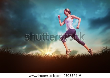 Pretty fit blonde jogging against blue sky over grass - stock photo