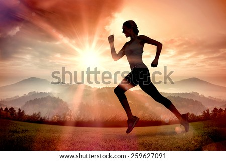 Pretty fit blonde jogging against sun shining over mountains - stock photo