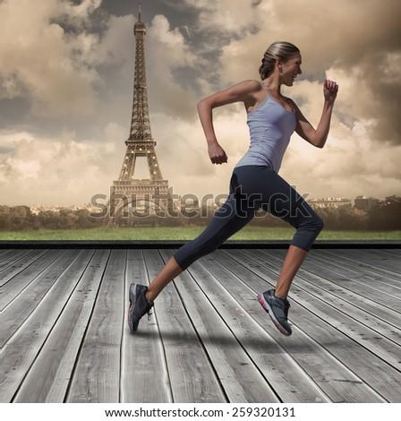 Pretty fit blonde jogging against wooden planks against paris - stock photo