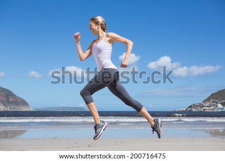 Pretty fit blonde jogging on the beach on a sunny day - stock photo