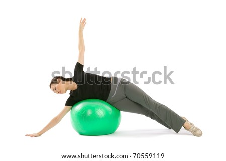 Pretty fit woman training with a pilates ball, isolated over a white background