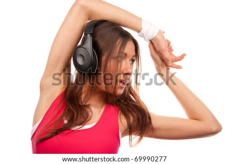 Pretty fitness brunette woman listening enjoying music in black modern headphones, smiling and laughing isolated on a white background - stock photo