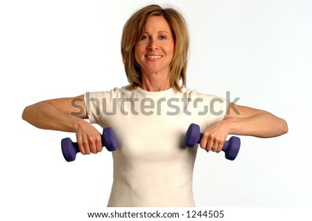 pretty fitness instructor with dumbbells SHOULDER RAISE - stock photo