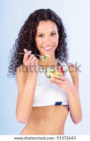 Pretty fitness woman holding salad on fork and plate