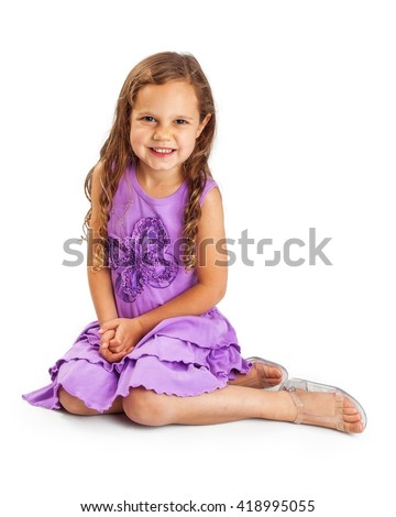 Pretty five year old girl with long blonde hair wearing purple dress sitting on white background - stock photo