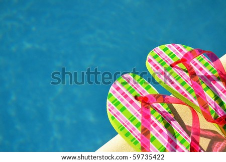 Pretty flip flops by the swimming pool. Room for your text. - stock photo