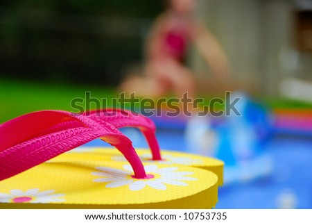 Pretty flip flops next to pool with girl running in distance - stock photo
