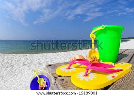 Pretty flipflops and beach buckets by shell collection on beach - stock photo